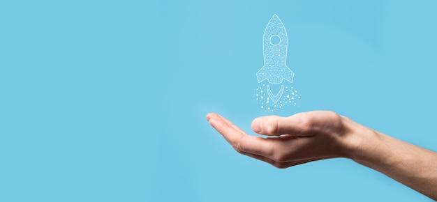 Männliche hand, die digitales transparentes raketensymbol hält. start-up geschäftsgeschäftskonzept