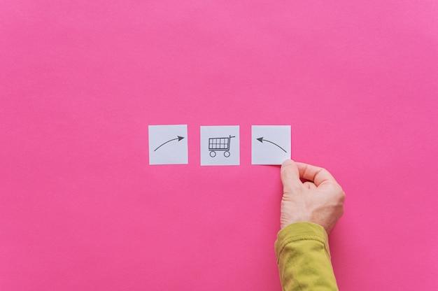 Männliche hand, die drei weiße post-it-papiere mit einkaufswagen und pfeilen, die darin zeigen, platziert
