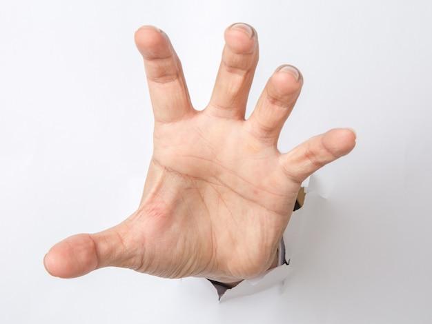 Männliche hand, die durch das papier locht