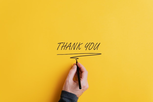 Männliche hand, die ein dankeschön schreibt