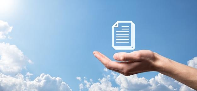 Männliche hand, die ein dokumentsymbol auf blauem hintergrund hält. dokumentenmanagement-datensystem-business-internet-technologie-konzept. unternehmensdatenmanagementsystem dms.