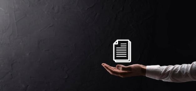 Männliche hand, die ein dokumentsymbol auf blauem hintergrund hält. dokumentenmanagement-datensystem-business-internet-technologie-konzept. unternehmensdatenmanagementsystem dms