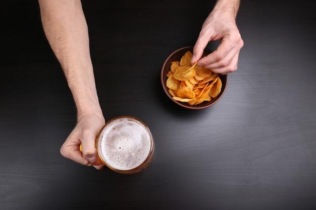 Männliche hand, die ein glas bier auf dunklem hintergrund hält