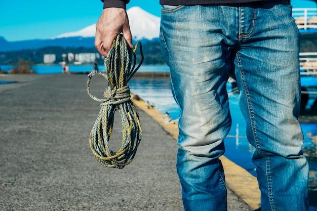 Männliche hand, die ein großes seil hält