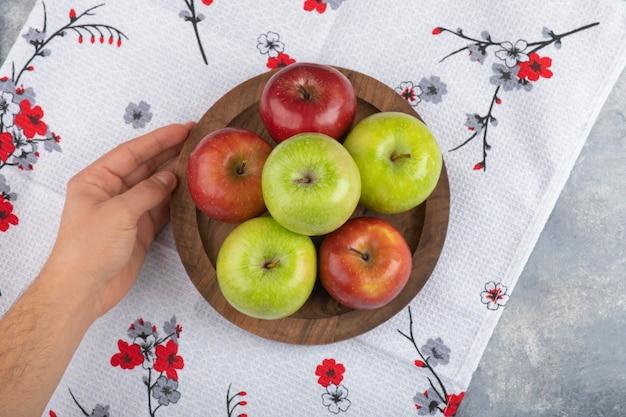 Männliche hand, die ein holzbrett mit frischen reifen grünen und roten äpfeln auf einer tischdecke hält.