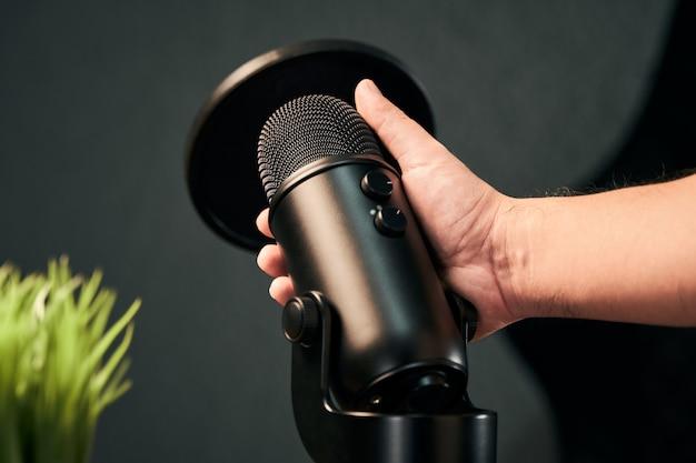 Männliche hand, die ein professionelles mikrofon hält