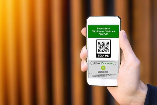 Männliche hand, die ein smartphone mit dem internationalen impfzertifikat covid-19 qr-code hält