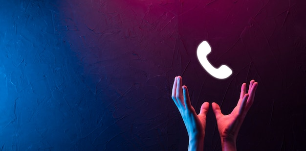 Männliche hand, die ein smartphone mit telefonsymbol hält. rufen sie jetzt an business communication support center customer service technology concept. neonrot, blauer lichthintergrund