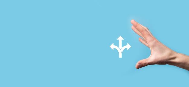 Männliche hand, die ein symbol mit drei richtungen auf blauem hintergrund hält. zweifel müssen zwischen drei verschiedenen optionen wählen, die durch pfeile angezeigt werden, die in die entgegengesetzte richtung weisen