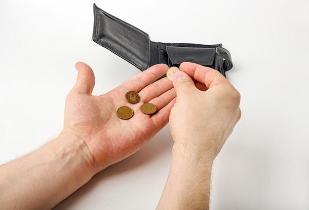 Männliche hand, die eine brieftasche öffnet und münzen auf weißem hintergrund zählt. weltwirtschaftskrise. finanzielles problem arbeitslosigkeit, insolvenzkonzept.