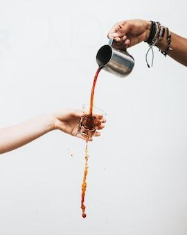 Männliche hand, die eine dunkle flüssigkeit in ein glas gießt, das von einer frau mit einem weißen hintergrund gehalten wird