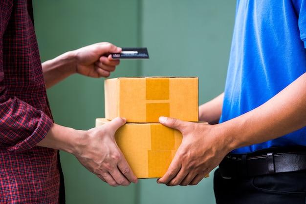 Männliche hand, die eine lieferung von kästen vom lieferboteen annimmt.