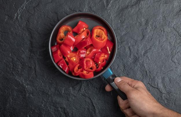Männliche hand, die eine pfanne mit in scheiben geschnittenen roten paprika auf schwarzem hintergrund hält