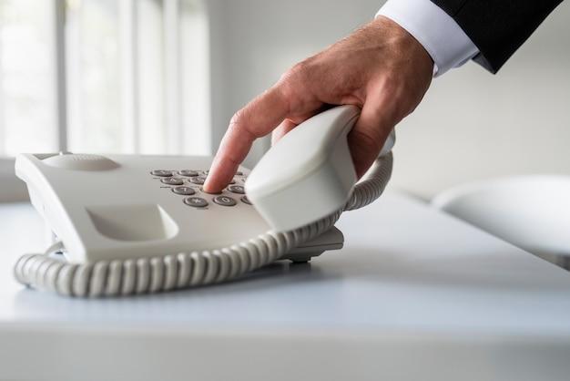 Männliche hand, die eine telefonnummer wählt, um einen anruf auf einem klassischen weißen festnetztelefon auf einem schreibtisch zu tätigen.