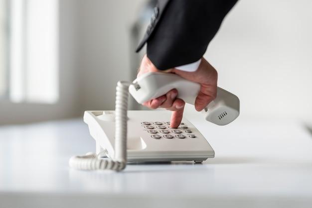 Männliche hand, die eine telefonnummer wählt, um einen anruf zu tätigen