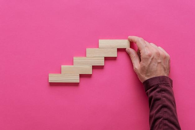 Männliche hand, die eine treppe wie struktur von holzstiften macht. konzeptionelles bild von wachstum und entwicklung.