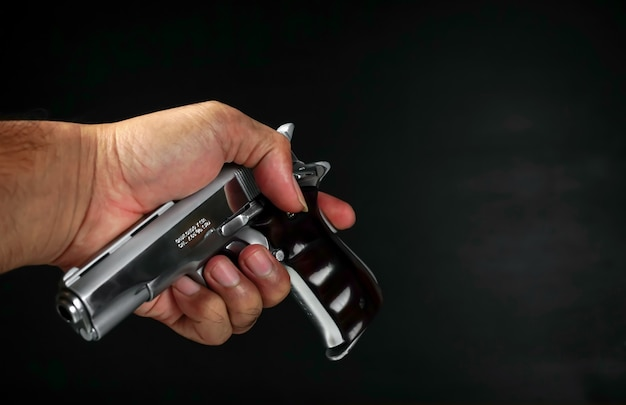 Männliche hand, die eine waffe auf schwarzem hintergrund hält eine waffe in der handverteidigung eines mannes