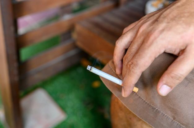 Männliche hand, die eine zigarette anhält