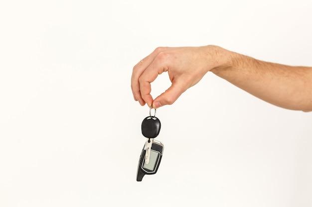Männliche hand, die einen autoschlüssel lokalisiert auf weiß hält