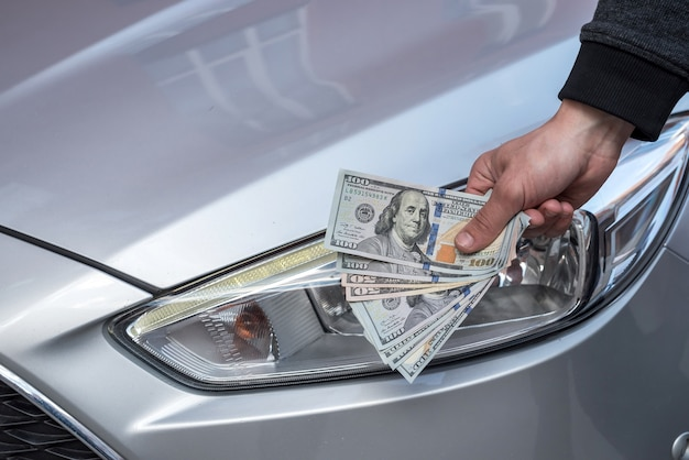 Männliche hand, die einen dollar für den kauf eines autos im autohaus zeigt. finanzen