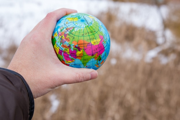 Männliche hand, die einen globus des planeten erde hält.