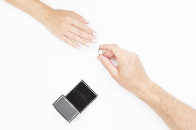 Männliche hand, die einen ring auf weibliche hand setzt