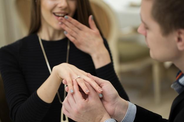 Männliche hand, die einen verlobungsring in einen finger einführt