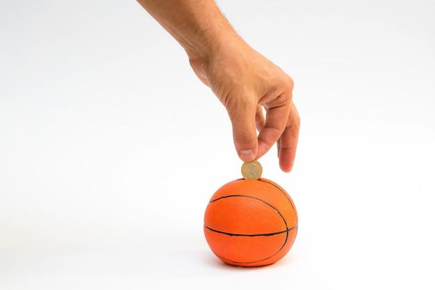 Männliche hand, die euro-münze in das sparschwein mit einer form des basketballs setzt