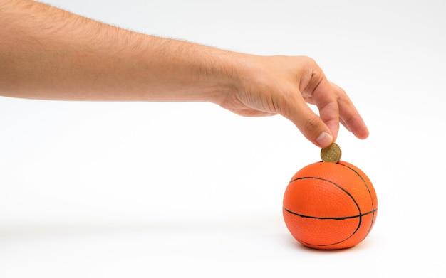 Männliche hand, die euro-münze in das sparschwein mit einer form des basketballs setzt.
