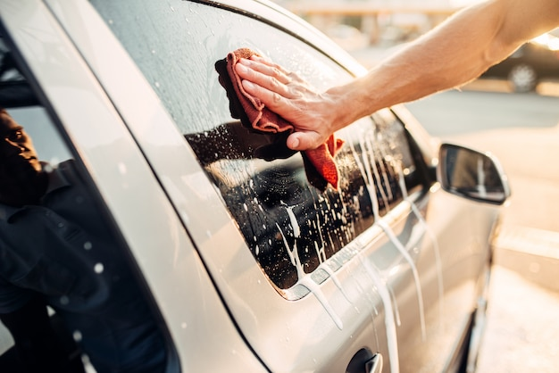 Männliche hand, die fahrzeugfenster mit schaum, auto in schaum, autowäsche reibt. autowaschstation