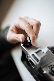 Männliche hand, die film retro kamera auf einem weißen tisch nachlädt. horizontal
