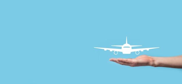 Männliche hand, die flugzeug-flugzeugikone auf blauem hintergrund hält. banner.nline ticketkauf.travel icons über reiseplanung, transport, hotel, flug und reisepass.flugticket buchungskonzept.