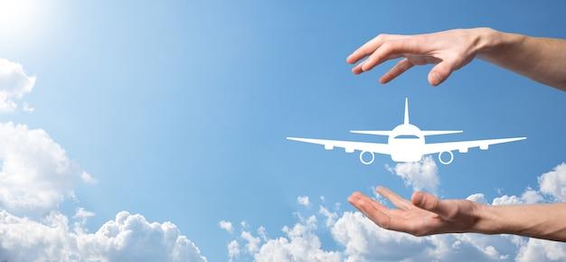 Männliche hand, die flugzeugflugzeugikone auf blauem hintergrund hält. banner.nline ticketkauf.reisesymbole über reiseplanung, transport, hotel, flug und reisepass.flugkartenbuchungskonzept.