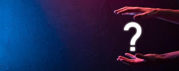 Männliche hand, die fragezeichen-symbol auf neonrotem, blauem, lila hintergrund hält. banner mit kopienraum. platz für text.