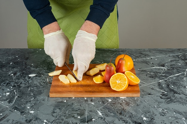 Männliche hand, die frische rote äpfel auf marmortisch schneidet.