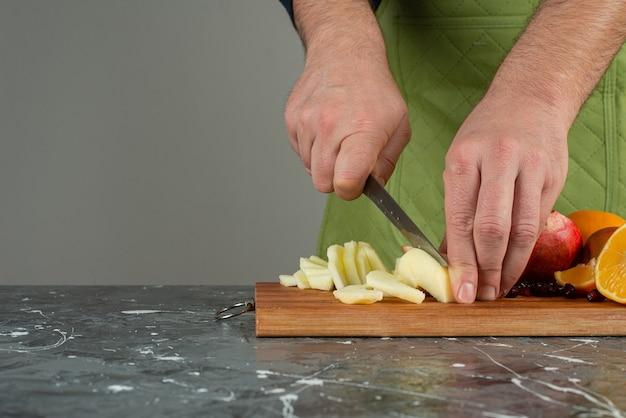 Männliche hand, die frischen apfel oben auf holzbrett auf tisch schneidet.