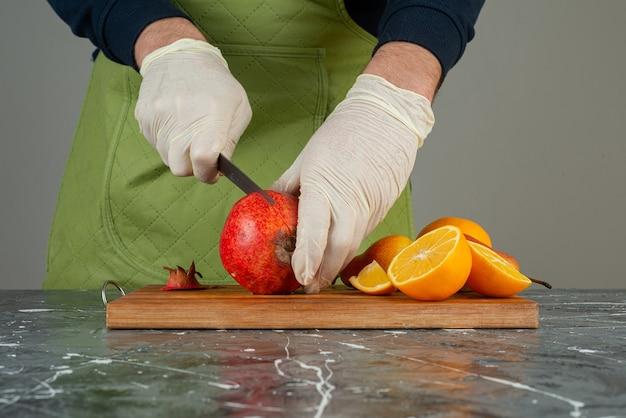 Männliche hand, die frischen granatapfel auf holzbrett auf tisch schneidet.