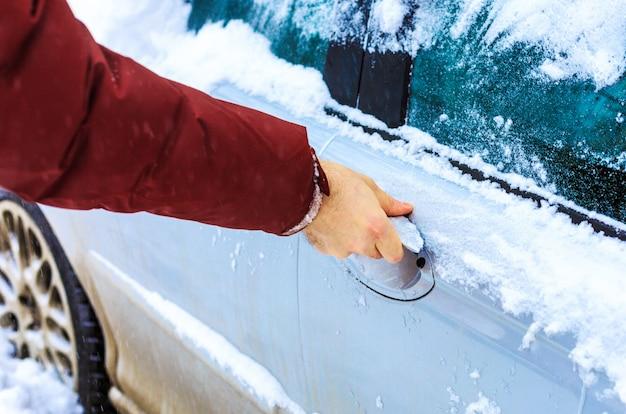 Männliche hand, die gefrorenen autoschloss entsperrt