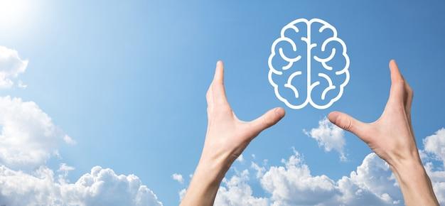 Männliche hand, die gehirnikone auf blauem hintergrund hält. künstliche intelligenz machine learning business internet technology concept.banner mit kopienraum.