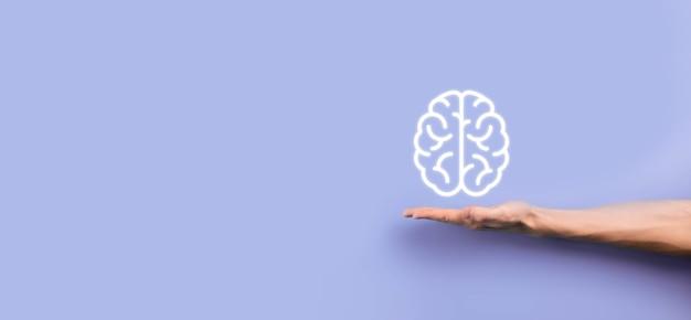 Männliche hand, die gehirnikone auf blauem hintergrund hält. künstliche intelligenz machine learning business internet technology concept.banner mit kopierraum