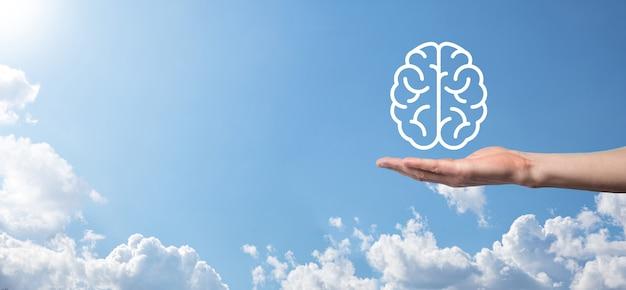 Männliche hand, die gehirnikone auf blauem hintergrund hält. künstliche intelligenz maschinelles lernen business internet technology concept.banner mit kopierraum.