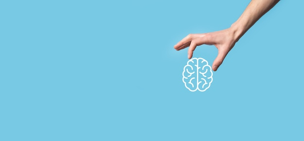 Männliche hand, die gehirnikone auf blauem hintergrund hält. künstliche intelligenz maschinelles lernen business internet technology concept.
