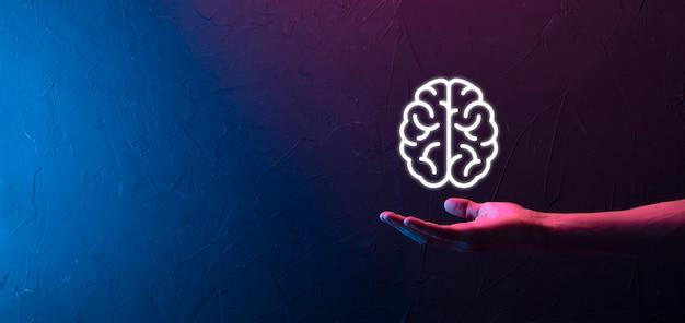 Männliche hand, die gehirnikone auf neonrotem, blauem hintergrund hält. künstliche intelligenz machine learning business internet technology concept.banner mit kopierraum