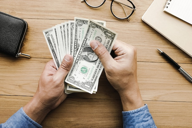 Männliche hand, die gelddollarschein auf holztisch durchlöchert.