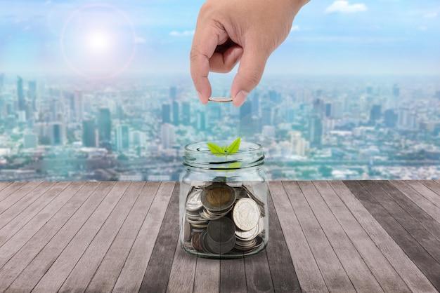Männliche hand, die geldmünzen in klare flasche und in kleinen baum auf hölzerne plankenkonzeptgeschäftsfinanzierung einsetzt