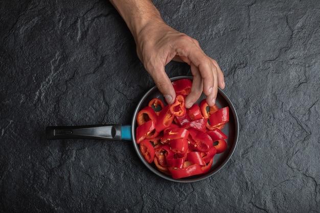 Männliche hand, die geschnittene rote paprika vom schwarzen hintergrund nimmt