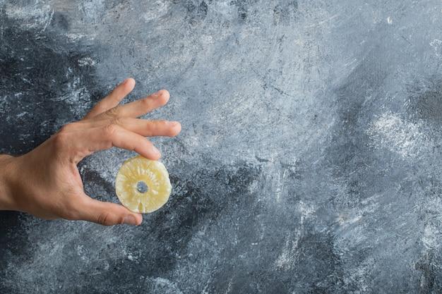 Männliche hand, die getrockneten ananasring auf marmorhintergrund hält