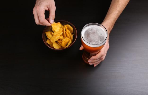 Männliche hand, die glas bier auf dunkelheit hält