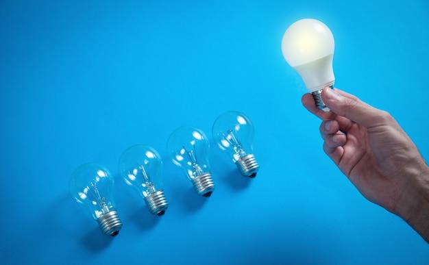 Männliche hand, die glühbirne im blauen hintergrund hält.