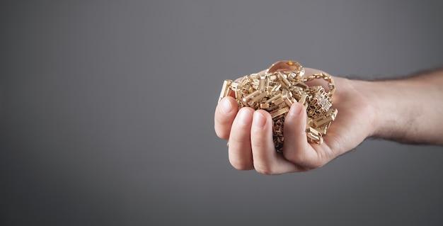 Männliche hand, die goldschmuck hält.